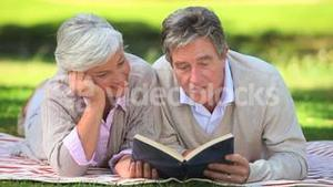 Mature couple reading a book outside
