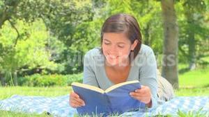 Young woman reading a book outside