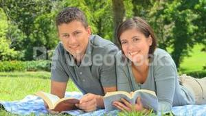 Smiling young couple reading outdoors