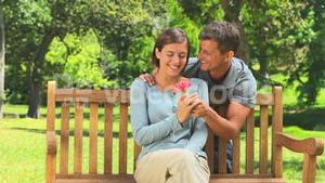 Young couple with a flower on a park bench