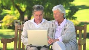Mature couple surfing on their laptop oudoors