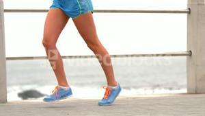 Female legs running by the sea