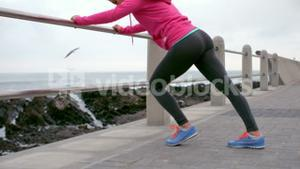 Fit woman stretching leg on railing