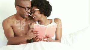 Smiling young couple reading book together