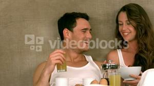 Pretty smiling couple eating breakfast