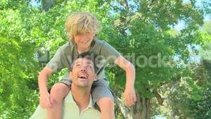 Young boy on his fathers shoulders