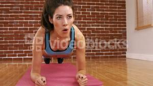 A fit woman on a plank position