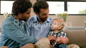 Gay smiling couple with their kid