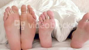 Bare feet of gay men couple in bed