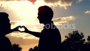 Silhouette of homosexual couple doing heart with hands together