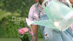 Smiling woman watering the plants