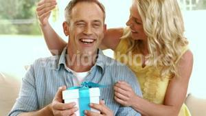 Happy mature couple with a gift box