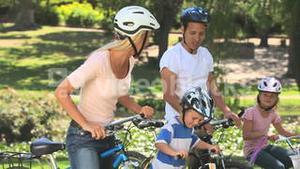 Young couple cycling with their two children