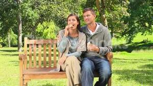 Young couple eating icecream on a public bench