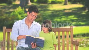 Father reading a book with his son
