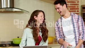 Smiling couple discussing over a tablet