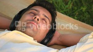 Man lying outdoors listening to music
