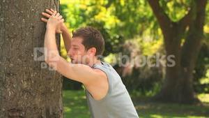 Athletic man leaning against a tree