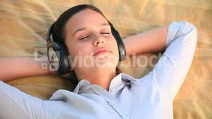Relaxed woman listening to music outdoors