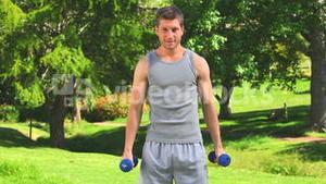 Athletic man doing exercises outdoors
