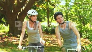 Athletic couple cycling in a wood