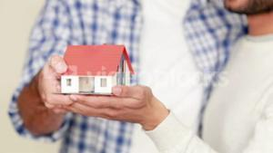 Homosexual couple holding miniature house model