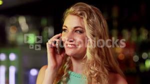 Smiling woman on phone in bar
