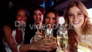 Happy friends drinking champagne in limousine