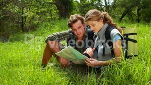 Hiker couple with map pointing ahead