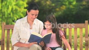 Mother and daughter reading outdoors