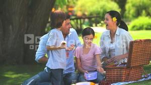 Happy family eating fruit outdoors