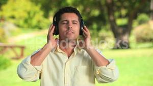 Smiling man listening to music outdoors