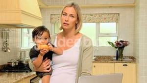 Tired young mother in kitchen trying to work on laptop holding baby