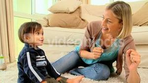 Mother and child laughing and playing on carpet