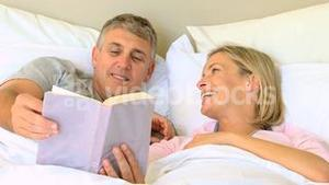 Couple in bed enjoying a book