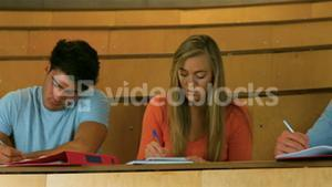 Classmates taking notes in library