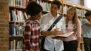 Standing classmates studying in library