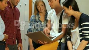 Smiling students using laptop in locker room