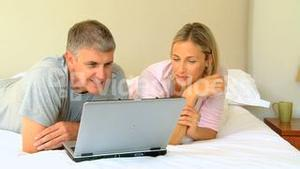 Couple relaxing on bed with a laptop