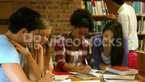 Smiling classmates studying in library