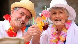 Mature couple with hats and garlands drinking cocktails