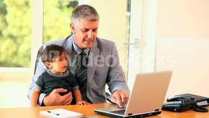 Baby helping father with laptop