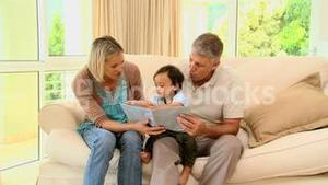 Couple showing their baby a childrens book