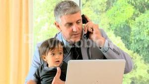 Man talking on phone while his baby is fidgeting on his lap