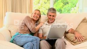 Happy couple relaxing with laptop