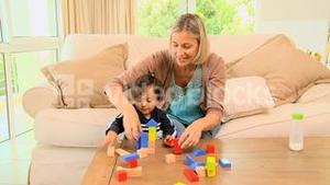 Young mother playing with her baby with building blocks