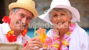 Senior couple with garlands drinking colored cocktails