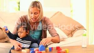 Young woman showing her baby how to play with building blocks