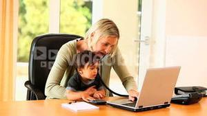 Baby helping mother with office work