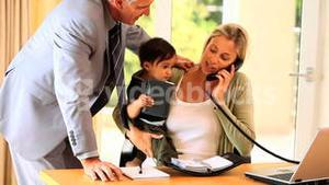 Woman struggling to do office work with baby on lap